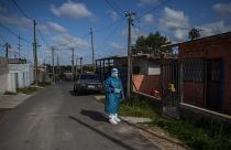 Un sanitario espera antes de hacer un test de covid en un barrio de Montevideo